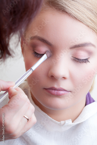 Make-up artist applying with brush color eyeshadow on female eye
