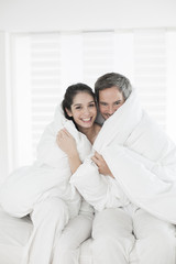 cheerful young couple wrapped in their quilt