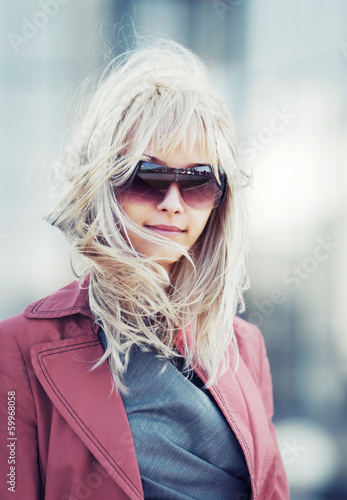 Blond woman in red jacket walking on the city street