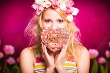 junge blonde Frau mit herzförmiger Geschenkbox