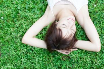 芝生の上に寝る女性