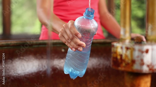 Young woman fillig a plastic bottle with healthy mineral water