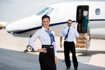 Confident Stewardesses Smiling With Pilot And Private Jet In Bac