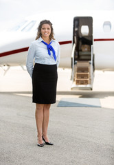 Beautiful Stewardess Standing Against Private Jet