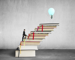 Businessman climbing on stack of books with growing bulb, buildi