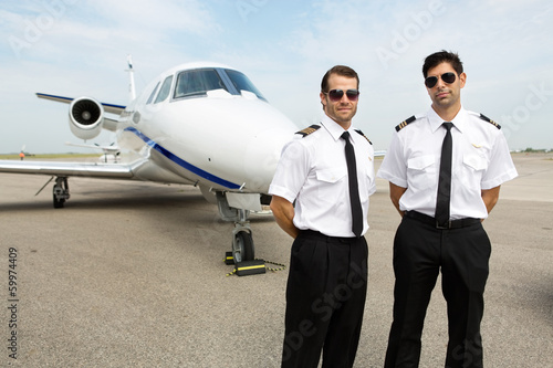 Pilots Standing In Front Of Private Jet - 59974409