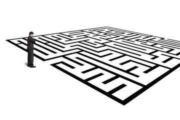 Businessman standing in front of maze isolated in white