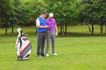 Golfer and caddy looking at a course guide