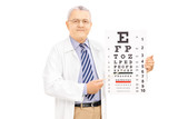 Middle aged male optician holding eyesight test and pointing wit