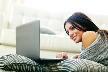 Happy smiling woman lying and using laptop at home