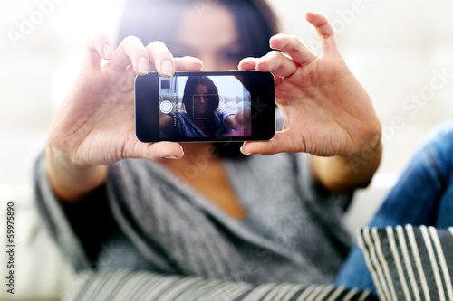 woman making self photo with smartphone. Focus on smartphone