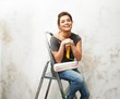 Happy beautiful young woman doing wall painting