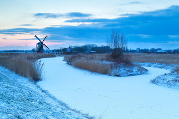 windmill and frozen river in snow