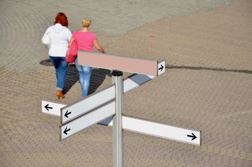 Clear signpost and two woman on the town square