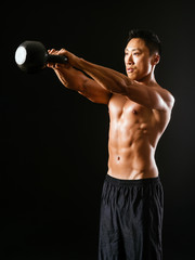 Muscular man working out with kettle bell