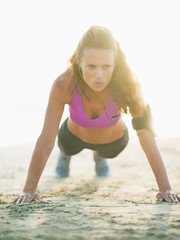 Healthy young woman doing push ups on beach