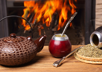Mate in the calabash, kettle, yerba on fire background