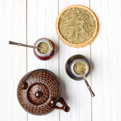 Yerba mate and calabashes on a light wooden background, top view