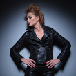 woman in leather jacket is looking to her side and down