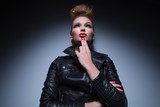 pensive fashion woman in leather jacket is looking away