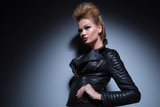 woman in leather clothes standing with hands on hips and looking