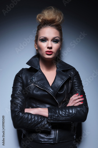 woman in leather jacket standing with arms crossed