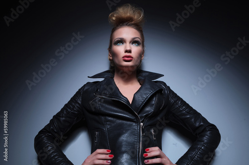 woman in leather jacket standing with hands on hips and looking