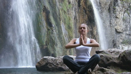 Woman meditating by the waterfall, Plitvice lakes, Croatia