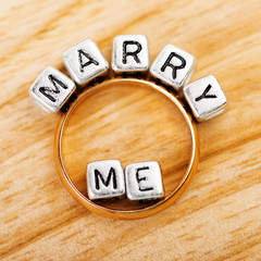 "Message ""Marry me"" and golden ring"