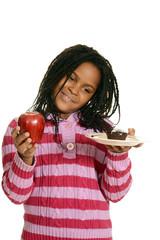 little girl choosing between cupake and apple