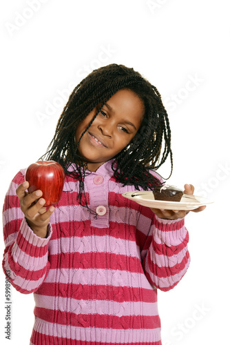 little girl choosing between cupake and apple