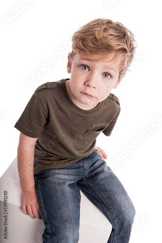 Boy Sitting on White Box.