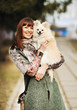 Young happy woman hold in hands small dog or puppy - outdoor por