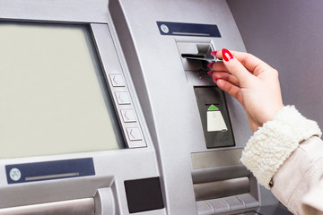 Woman using credit card to withdraw cash money