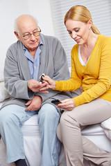 Frau macht Blutzuckermessung bei einem Senioren