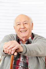 Senior lächelt mit Gehstock