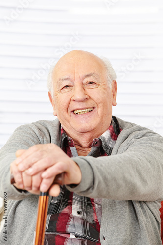 canvas print picture Senior lächelt mit Gehstock
