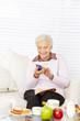 Seniorin liest Nachricht auf Smartphone