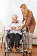 Frau gibt Brille an Seniorin im Rollstuhl