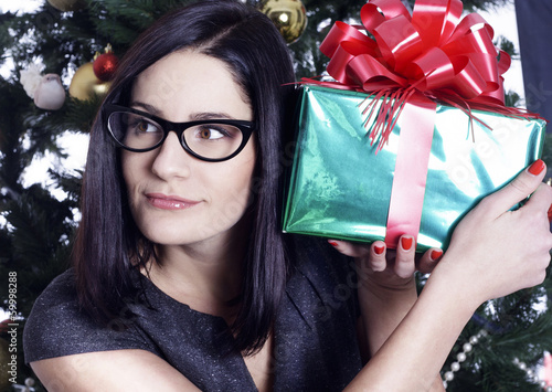Pretty business woman near christmas tree with present