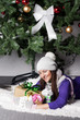 Young woman near xmas tree with presents