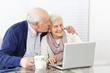 Mann küsst Seniorin mit Laptop