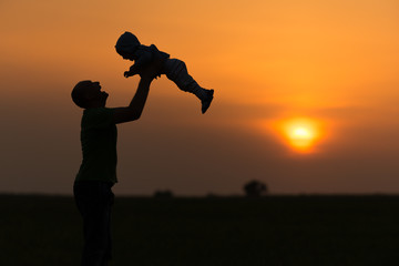 Dad throws the baby at sunset