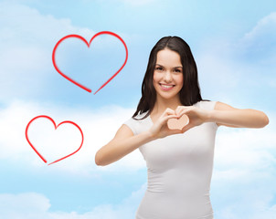 smiling girl showing heart with hands