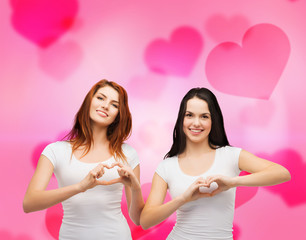 two smiling girls showing heart with hands