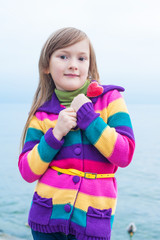 Beautiful little girl in colorful jacket, holding red heart