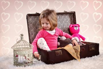 blondes Mädchen spielt im Koffer