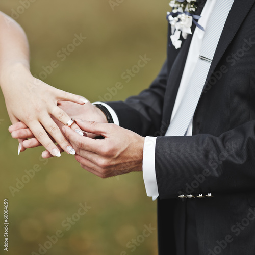 Hands of wedding couple putting golden rings