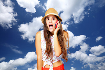 surprised girl talking on mobile phone. Sky background.