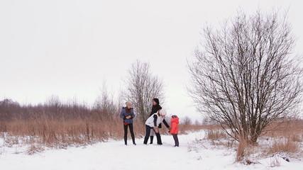 девушки и дети веселятся зимой на природе